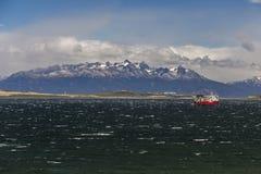Paesaggio del mare con una nave sul grande fondo maestoso delle montagne della neve Manica del cane da lepre, Ushuaia, Argentina fotografia stock libera da diritti