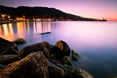 Paesaggio del mare durante l'alba con gli indicatori luminosi della città Fotografia Stock