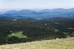 Paesaggio del paesaggio della montagna con cielo blu sopra vegetazione arborea Immagini Stock