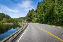 Paesaggio del paese con lake& x27; riva di s e strada vuota della strada principale Immagini Stock