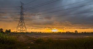 Paesaggio del palo ad alta tensione in giacimento e cielo del riso Fotografia Stock Libera da Diritti