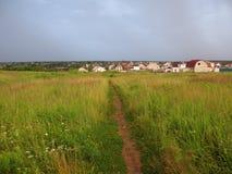 Paesaggio del pascolo con il sentiero per pedoni prima della tempesta Immagine Stock