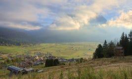 Paesaggio del pendio di collina di autunno nel primo mattino con le nuvole dorate che abbracciano montagna Zugspitze nei preceden Fotografia Stock Libera da Diritti