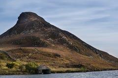 Paesaggio del picco ripido della collina con la piccola rimessa per imbarcazioni sul lago dentro per Immagine Stock Libera da Diritti
