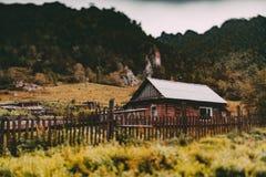 Paesaggio del tiltshift di caduta con la casa e le montagne coutry Fotografie Stock Libere da Diritti