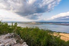 Paesaggio del villaggio dal castello sulla collina Lago in priorità alta Cielo drammatico Immagini Stock Libere da Diritti