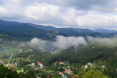 Paesaggio del villaggio di mattina nella foresta coperta di fogg Immagine Stock