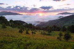 Paesaggio dell'alba alle alte montagne Nebbia densa con bella luce Un posto da rilassarsi nel parco carpatico fotografie stock