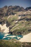 Paesaggio dell'alta montagna con il lago e l'alto picco Immagine Stock