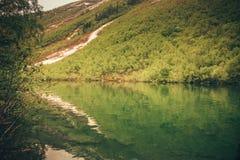 Paesaggio dell'alta montagna con il lago e l'alto picco Fotografia Stock