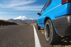 Paesaggio dell'alta montagna con un'automobile blu sul bordo della strada Caucaso del nord Fotografia Stock