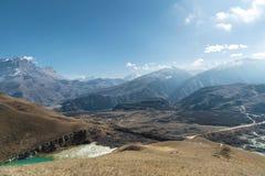 Paesaggio dell'alta montagna del Caucaso del nord Un'istantanea dall'altezza di un lago e di una strada non asfaltata su un fondo Fotografia Stock