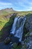 Paesaggio dell'Islanda con l'alta cascata fra verde Immagine Stock