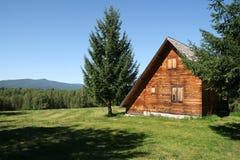 Paesaggio della campagna con una casa di legno adorabile fotografia stock