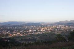 Paesaggio della città con il fondo del cielo e della montagna fotografie stock libere da diritti