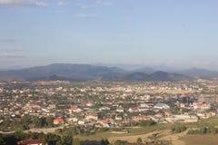 Paesaggio della città con la casa bluiding del cielo blu e della montagna immagini stock libere da diritti