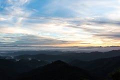 Paesaggio della foresta della montagna sotto il cielo di alba con le nuvole Fotografia Stock