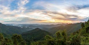 Paesaggio della foresta della montagna sotto il cielo di alba con le nuvole Immagini Stock