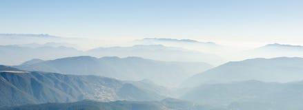 Paesaggio della gamma di montagne con la nebbia di mattina Fotografia Stock
