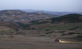 Paesaggio della montagna al crepuscolo con funzionamento della mietitrebbiatrice Immagini Stock Libere da Diritti