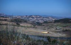 Paesaggio della montagna al crepuscolo con funzionamento della mietitrebbiatrice Immagine Stock