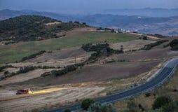 Paesaggio della montagna al crepuscolo con funzionamento della mietitrebbiatrice Fotografie Stock Libere da Diritti