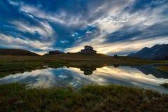 Paesaggio della montagna al tramonto vicino ad una capanna alpina Fotografia Stock Libera da Diritti