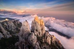 Paesaggio della montagna Alte rocce con le nuvole basse al tramonto Immagini Stock