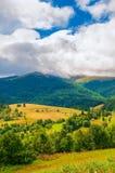 Paesaggio della montagna carpatica con il cielo nuvoloso blu nel giorno di estate Immagini Stock
