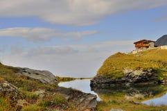 Paesaggio della montagna con il chalet della montagna e dello stagno Fotografia Stock