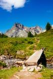 Paesaggio della montagna con il fiume ed il ponte di legno, Alpe Devero,  Fotografia Stock Libera da Diritti
