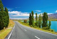 Paesaggio della montagna con il lago e la strada Fotografia Stock