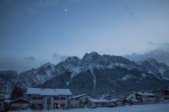 Paesaggio della montagna con il massiccio ed il villaggio della montagna nell'orario invernale alla notte Fotografia Stock