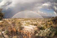 Paesaggio della montagna con l'arcobaleno e le nuvole Immagine Stock