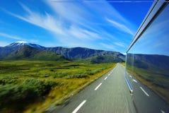Paesaggio della montagna con l'automobile di movimento sulla strada asfaltata Fotografia Stock