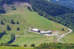 Paesaggio della montagna con la strada ed i cottage Villaggio in montagna va Fotografie Stock Libere da Diritti
