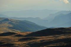 Paesaggio della montagna con le colline nella priorità bassa Fotografia Stock