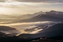 Paesaggio della montagna con nebbia e le case Immagine Stock