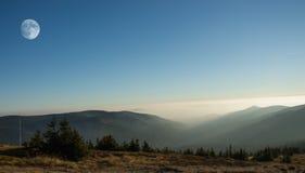 Paesaggio della montagna con sorgere della luna Giorno nebbioso Fotografia Stock