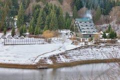 Paesaggio della montagna con un hotel ed i posti di campeggio vicino ad un fiume Immagini Stock Libere da Diritti
