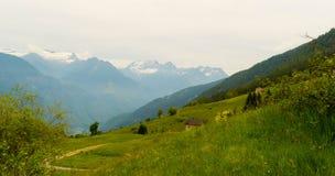 Paesaggio della montagna con una casa nelle alpi svizzere di estate Fotografia Stock