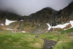 Paesaggio della montagna di estate nelle alpi di Transylvanian, con le nuvole piovose nebbiose Immagine Stock