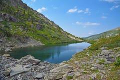 Paesaggio della montagna di estate: Pietre intorno al Tarn freddo profondo Immagine Stock