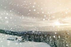 Paesaggio della montagna di inverno Vecchie case di legno su schiarimento nevoso sul fondo della cresta della montagna, della for immagine stock