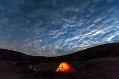 Paesaggio della montagna di notte con la tenda illuminata Fotografia Stock