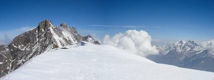 Paesaggio della montagna di panorama nelle alpi svizzere vicino a Zermatt un bello giorno nell'inverno tardo sotto un cielo blu Fotografie Stock Libere da Diritti