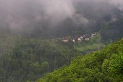 Paesaggio della montagna poco tempo dopo la pioggia di molla Alpi slovene Forest Road, albero venerabile, nebbia, nuvole e picchi Immagini Stock