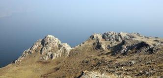 Paesaggio della montagna, rocce vulcaniche nella priorità alta contro il cielo blu di autunno in una foschia Immagine Stock