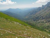Paesaggio della montagna rocciosa con i massi su un prato e un cielo blu e le nuvole immagine stock libera da diritti