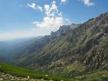 Paesaggio della montagna rocciosa con il prato ed il cielo blu e le nuvole immagine stock